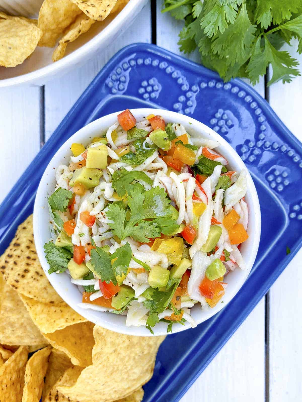 Closeup of crab ceviche in white bowl with chips on the side.