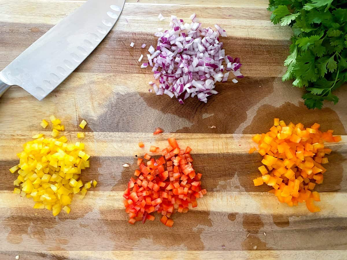 Diced peppers and onions on cutting board.