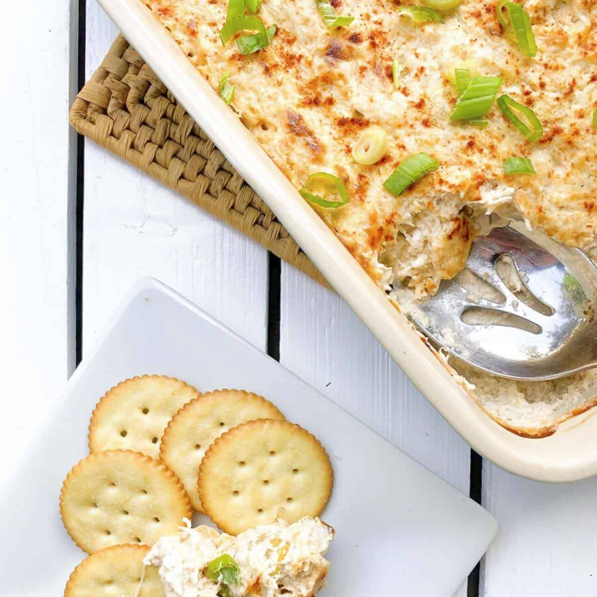 Hot crab artichoke dip baked in casserole dish scooped onto plate with crackers.