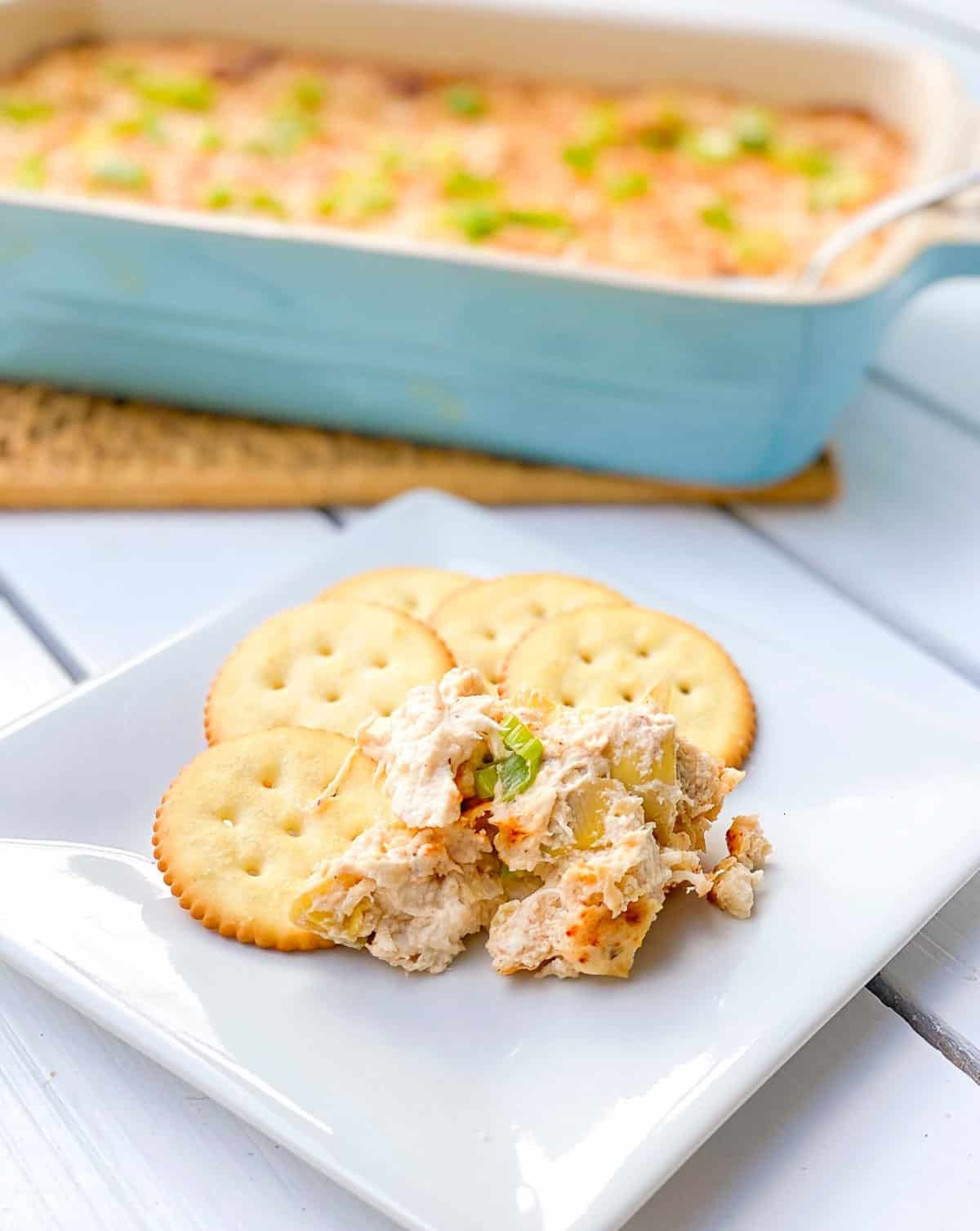 Crab artichoke dip in baking dish and on crackers on a plate.