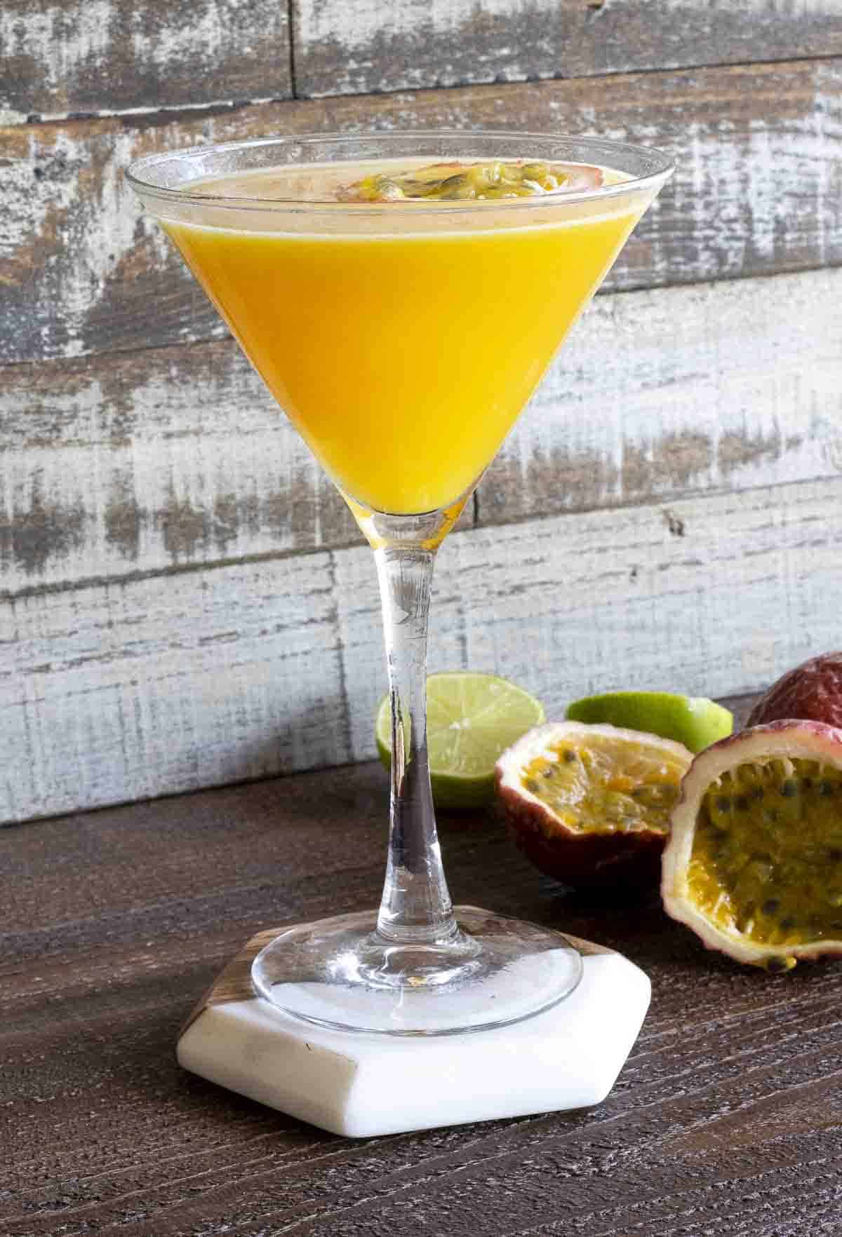 Passion fruit martini in a martini glass with limes and passion fruit on table.