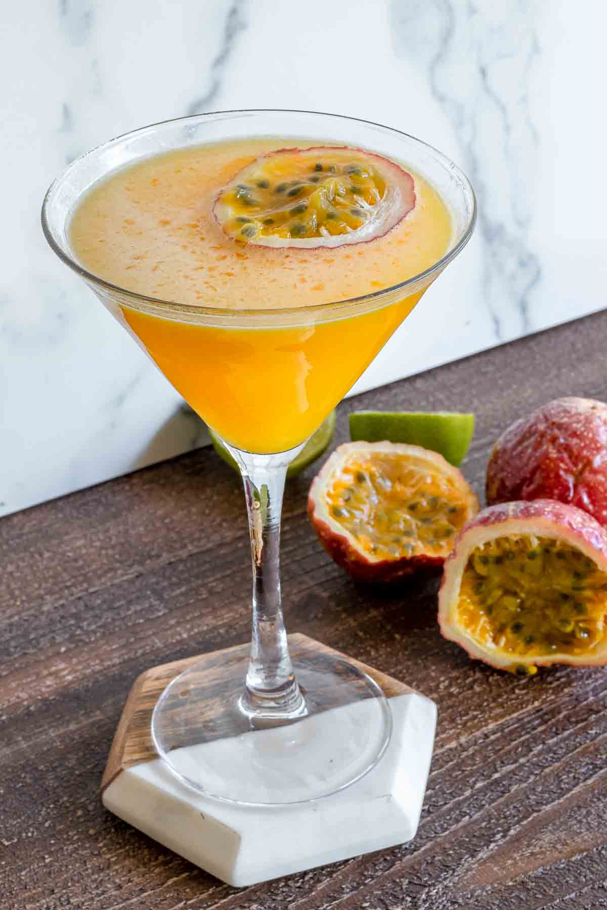 Passion fruit and vodka martini in a martini class with passion fruit slice floating.