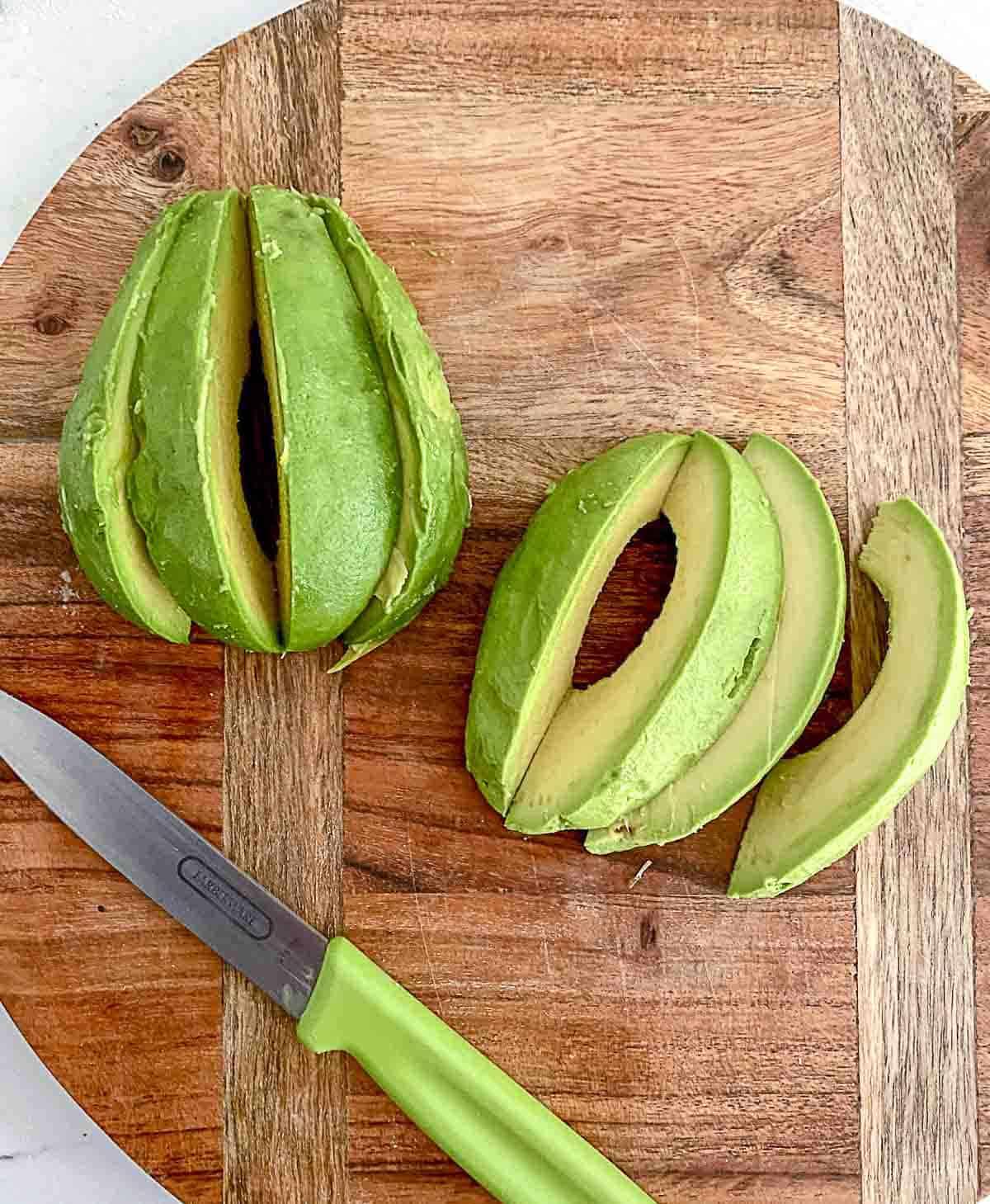 Avocado sliced on cutting board.