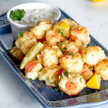 Fried crab stick bites on plate with seasoning and lemons.