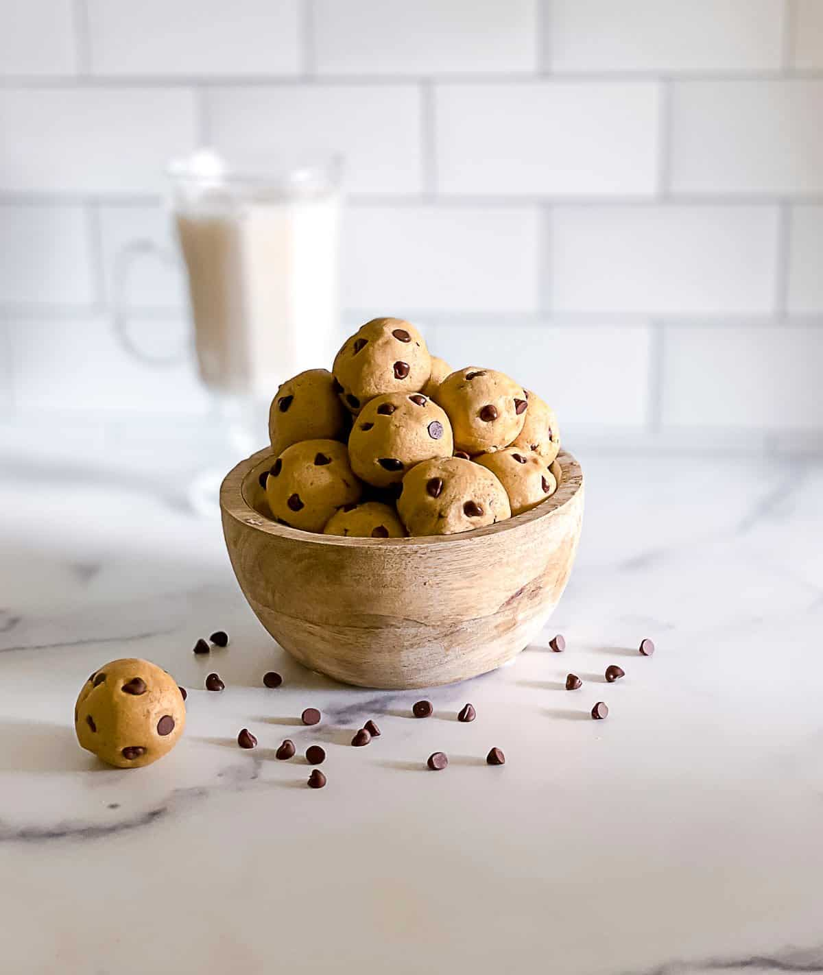 Mini chocolate chip cookie dough balls in a bowl with chocolate chips around it.