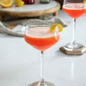 Aperol gin sour cocktail on table with lemon peel on rim.