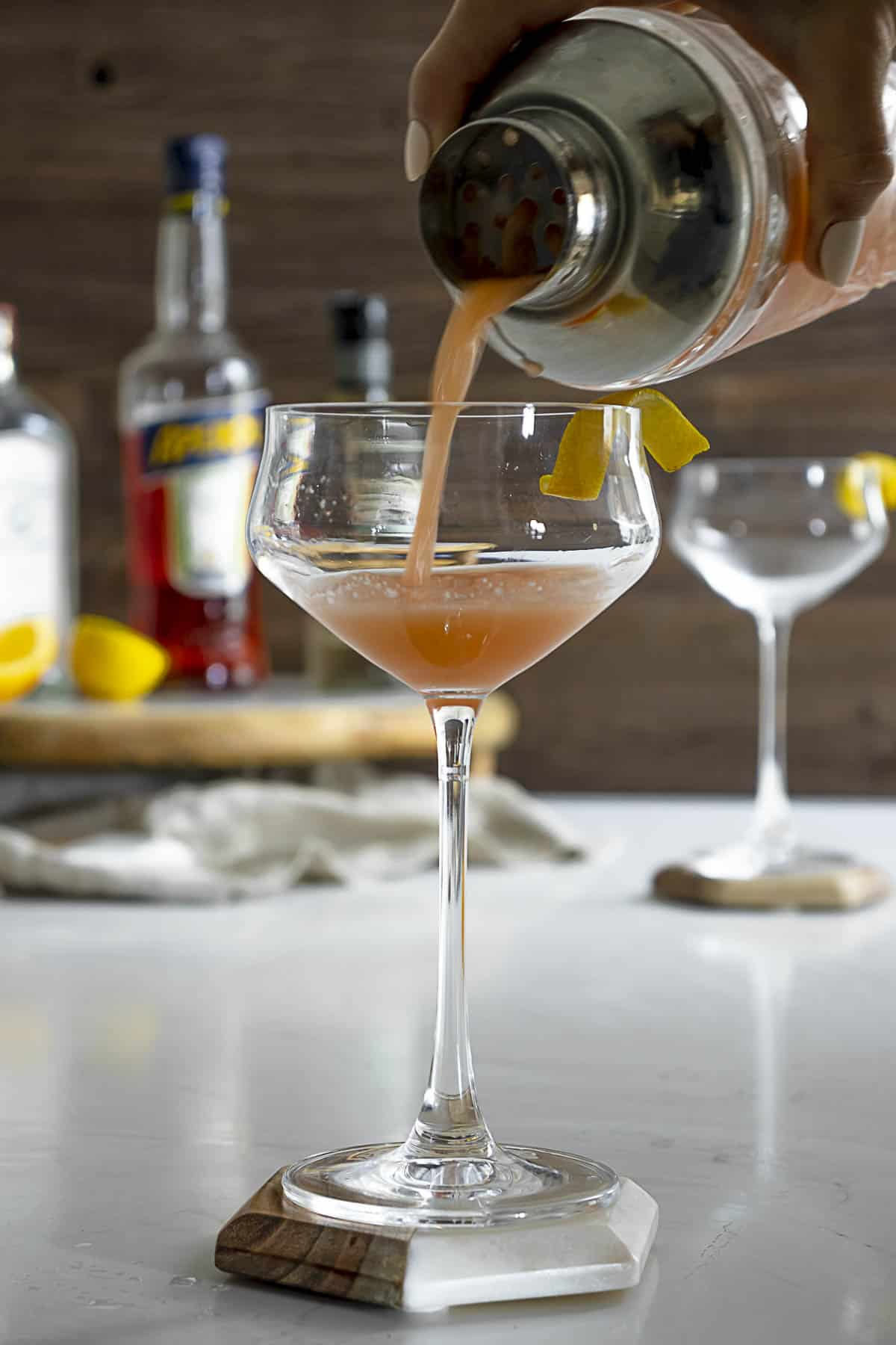 Pouring an Aperol sour with gin into a coupe glass.