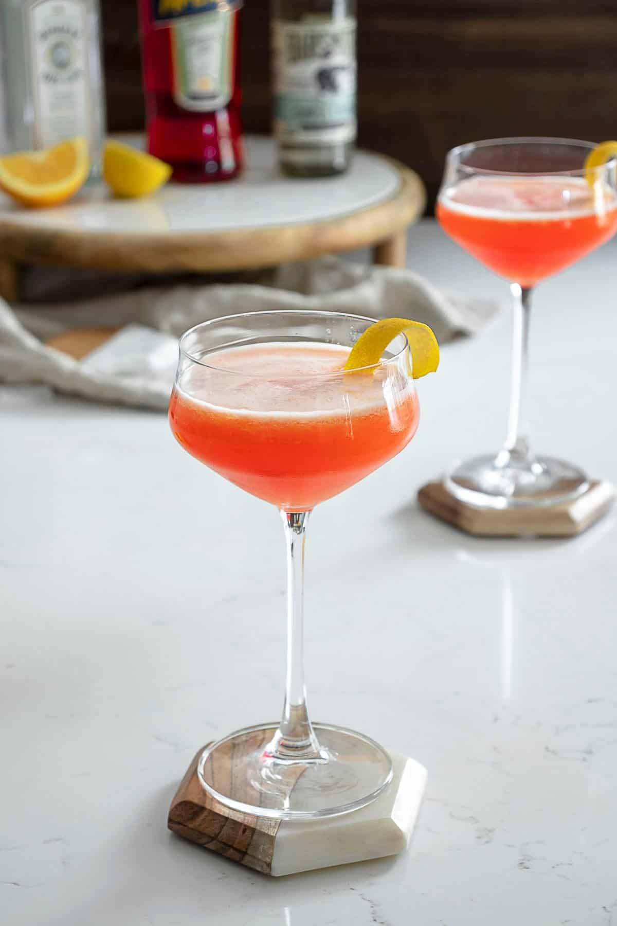 Aperol gin sour on table with lemon peel.