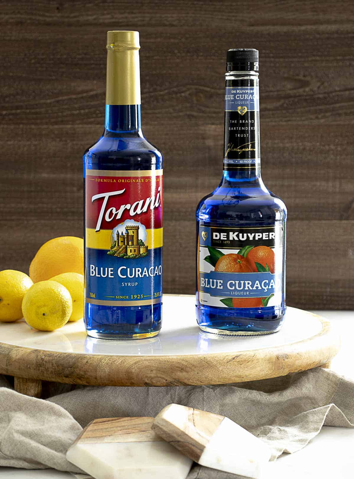 Bottle of blue curacao syrup and blue curacao liqueur next to one another.