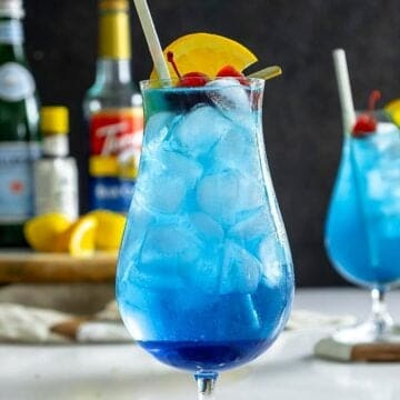 Blue lagoon mocktail recipe on table with cherry and orange slice.