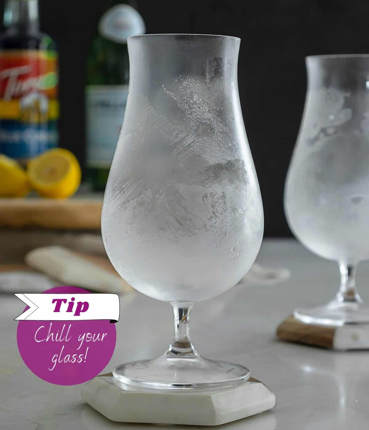 A chilled hurricane glass on table.