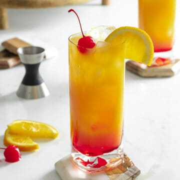 Vodka sunrise cocktail on table with cherry and orange slice.
