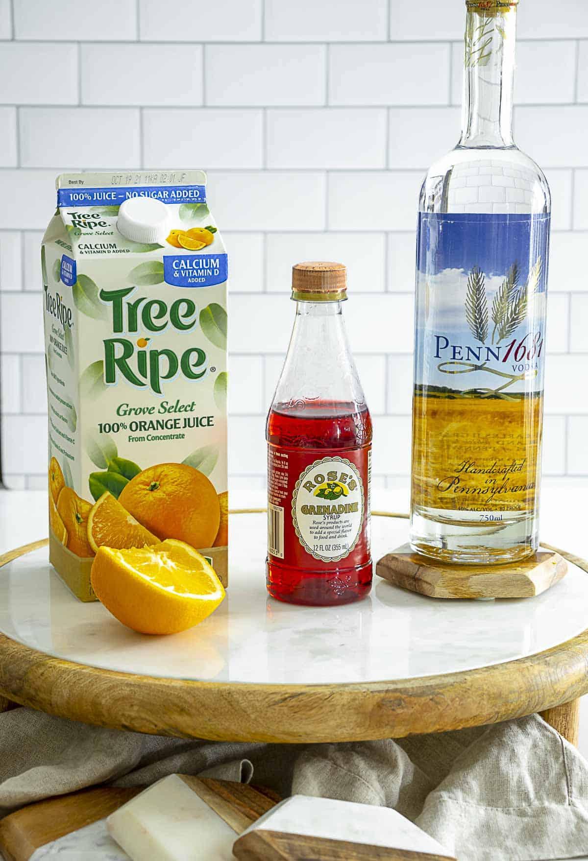 Orange juice, grenadine and vodka on table with orange.