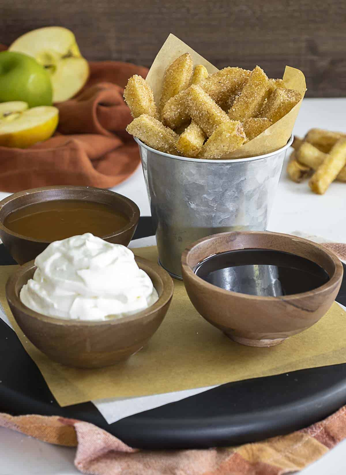 Apple fries in a cup on a cutting board with chocolate sauce, caramel sauce and whipped cream for dipping.