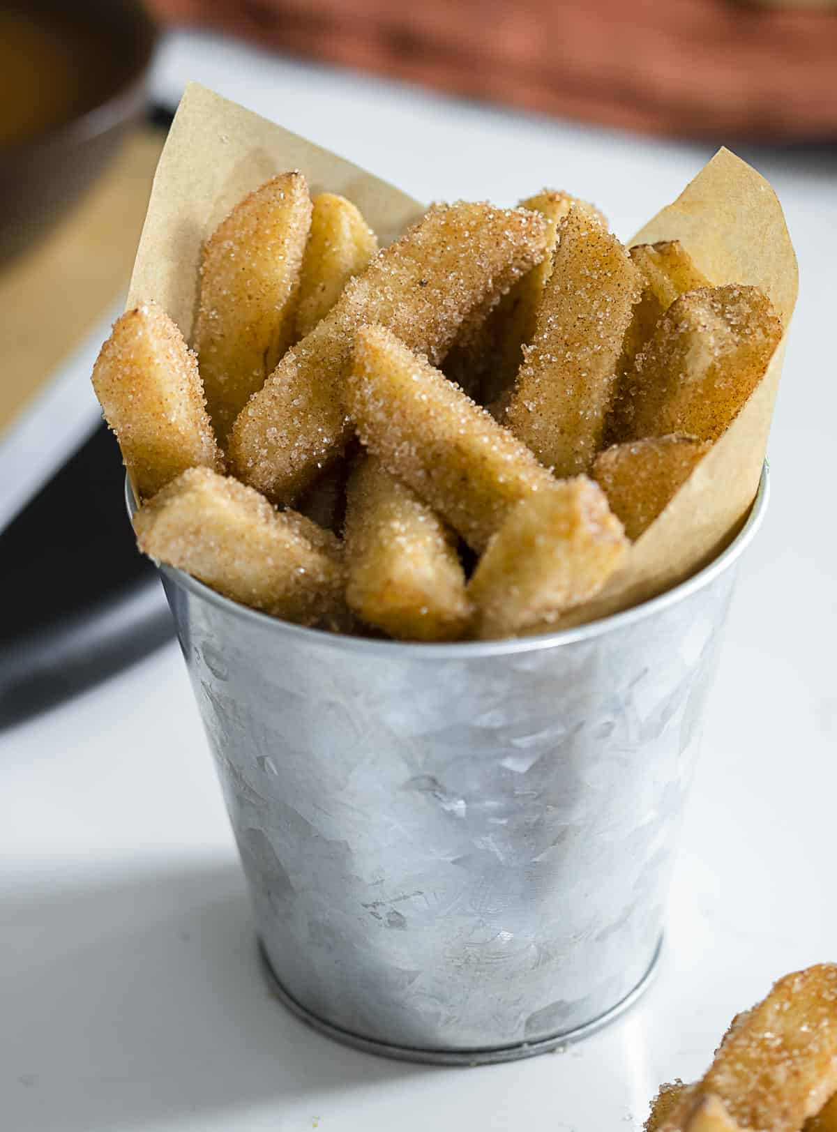 Cinnamon sugar fried apple fries in a cup on table.