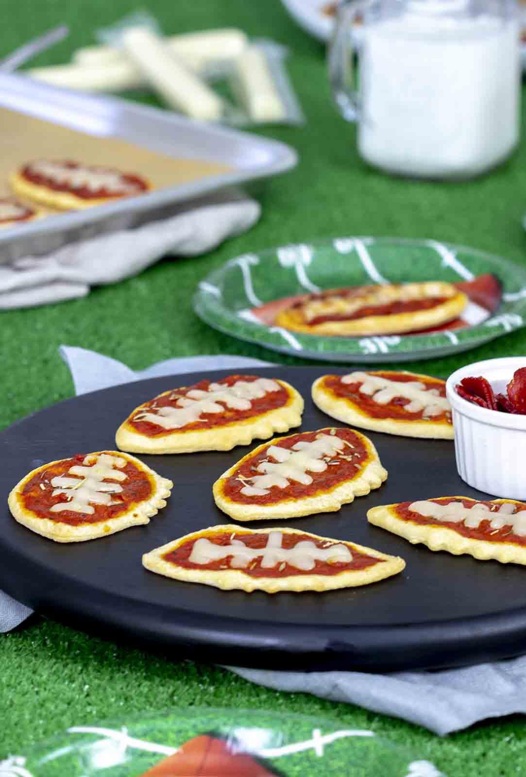 Mini pizza footballs on cutting board with football backdrop.