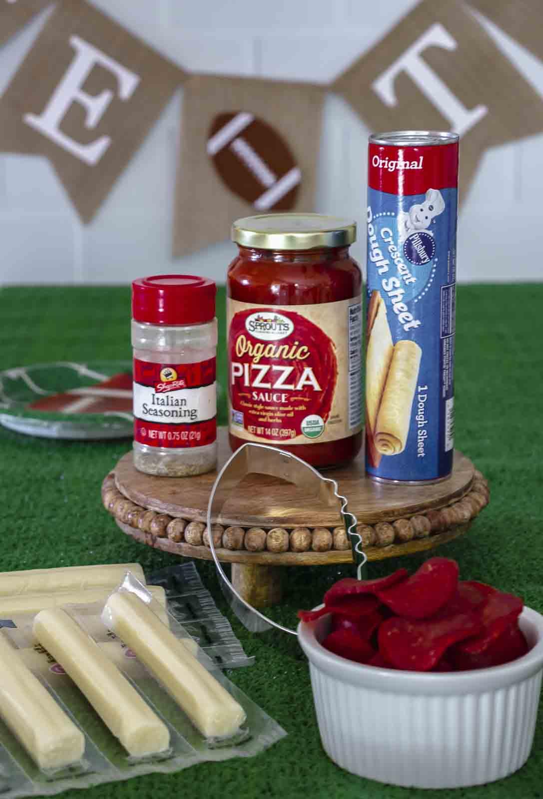 Ingredients to make mini football pizzas on fake grass.