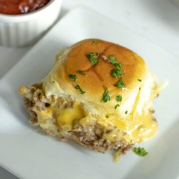 Close up of Philly cheesesteak Hawaiian roll pull apart sliders on white plate.