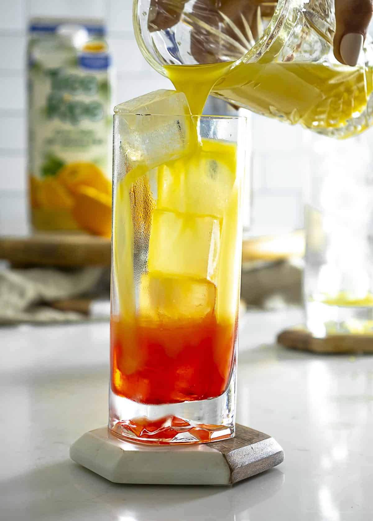 Pouring orange juice to top of drink.