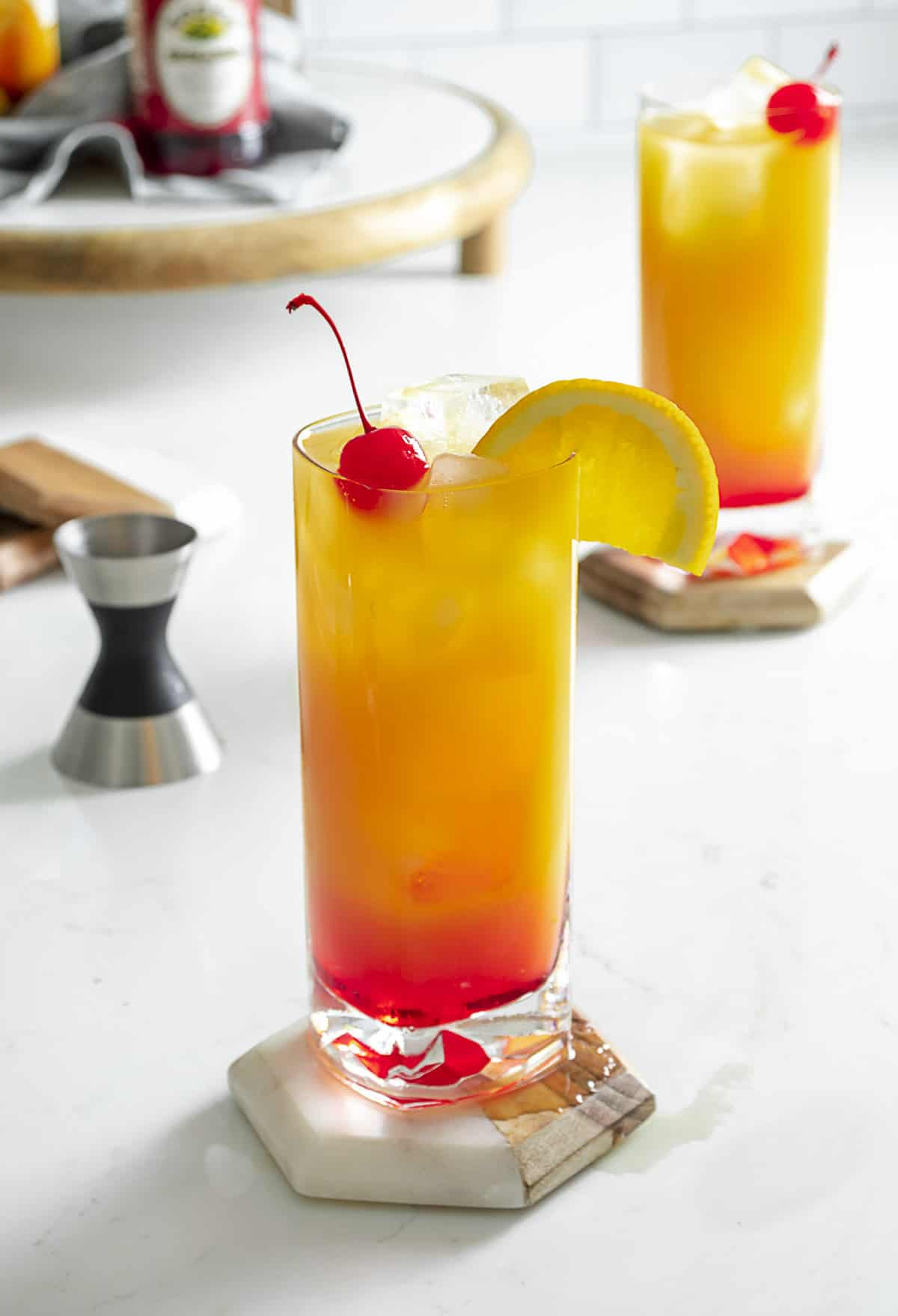 Two vodka sunrise cocktails on table with cherry and orange slice for garnish.