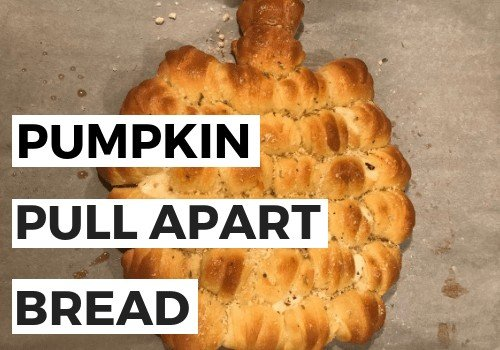 Bread shaped into a pumpkin and baked on baking sheet.
