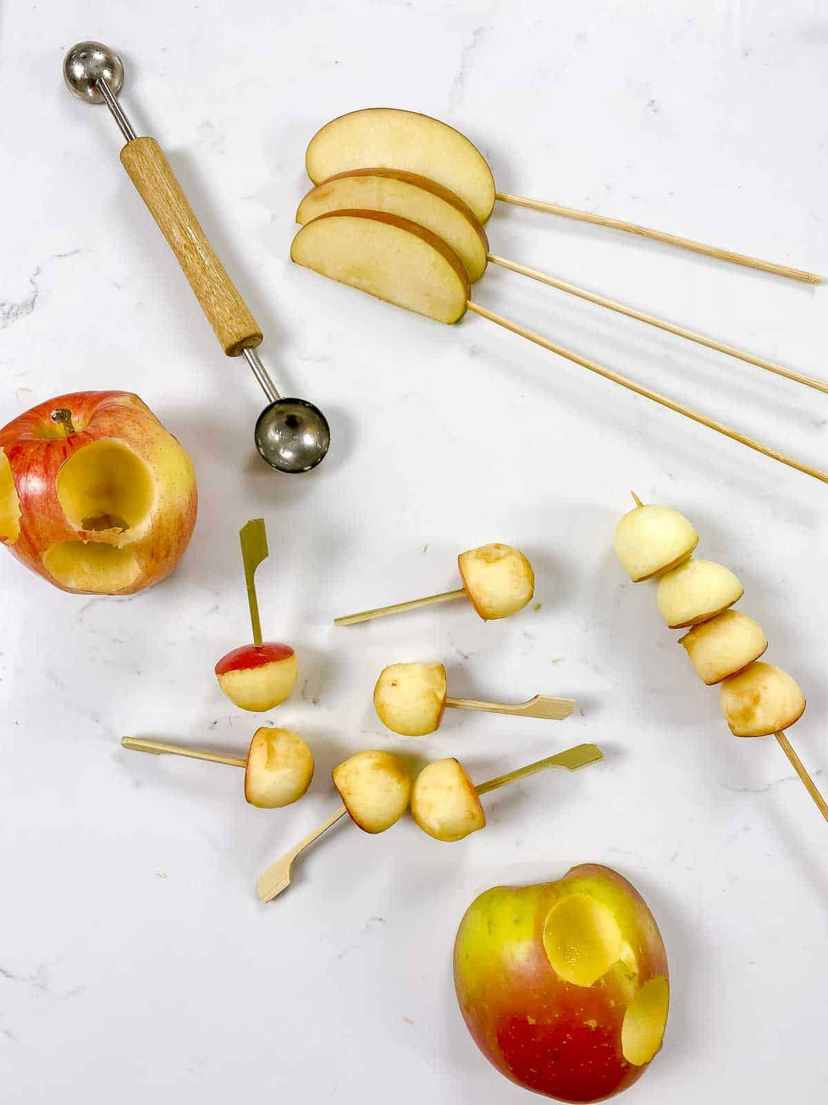 Showing how to melon ball an apple to make mini caramel apple skewers.
