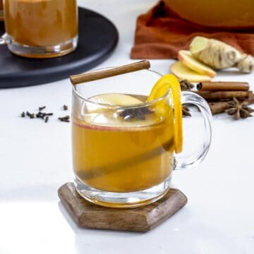 Hot mulled apple cider in clear mug with spiced and orange.
