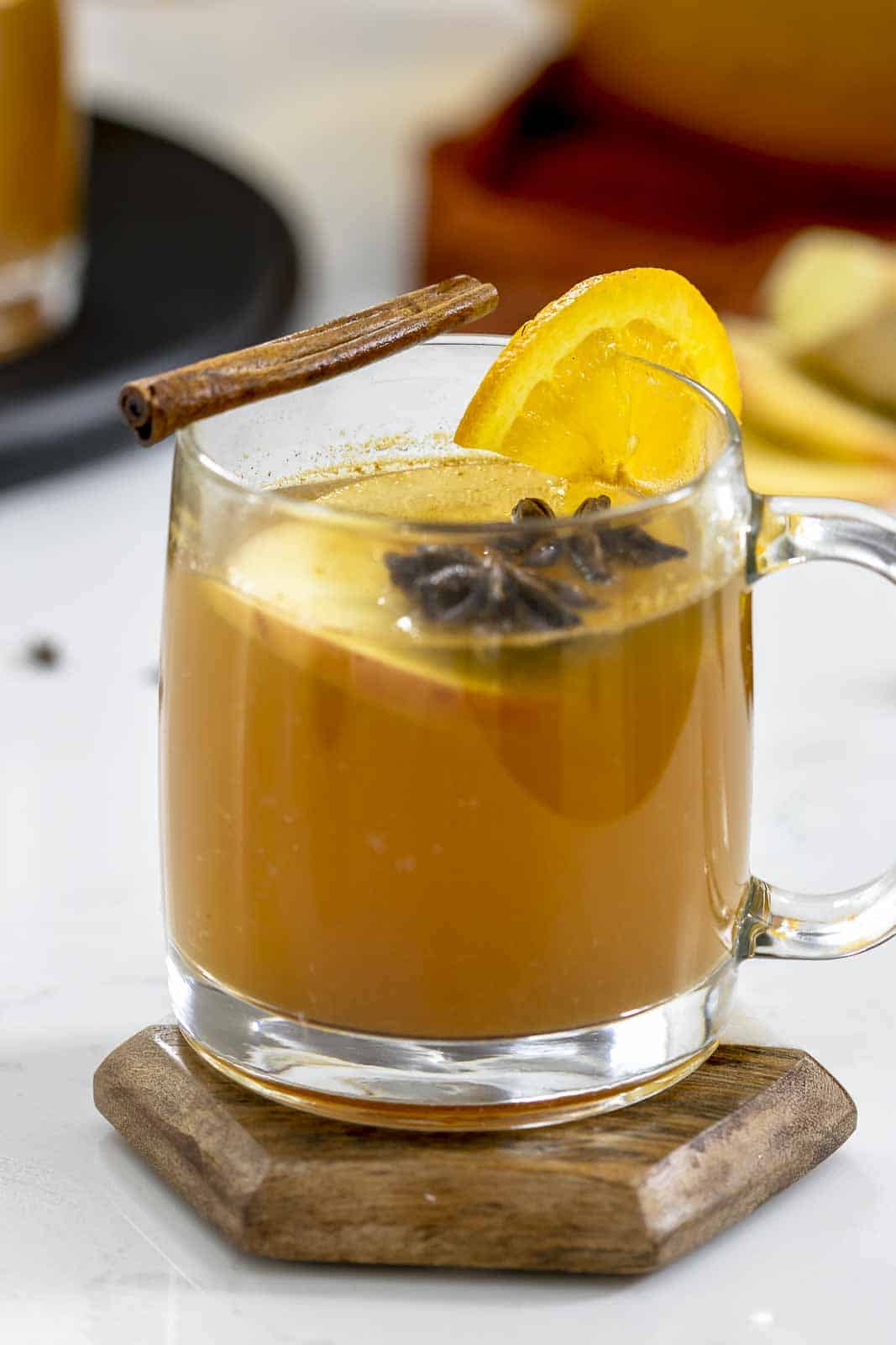 Hot mulled spiked apple cider in a clear mug.