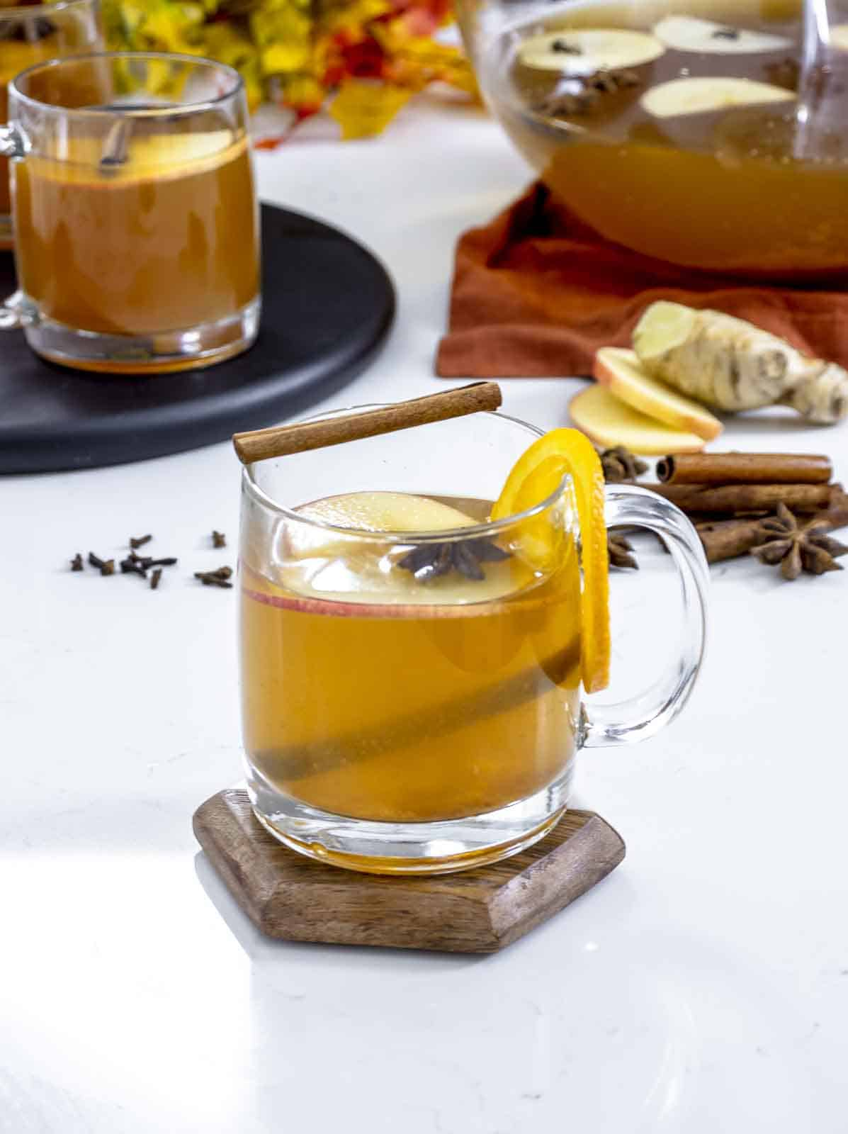 Hot mulled apple cider in a clear mug garnished with orange and cloves and spiked with rum.