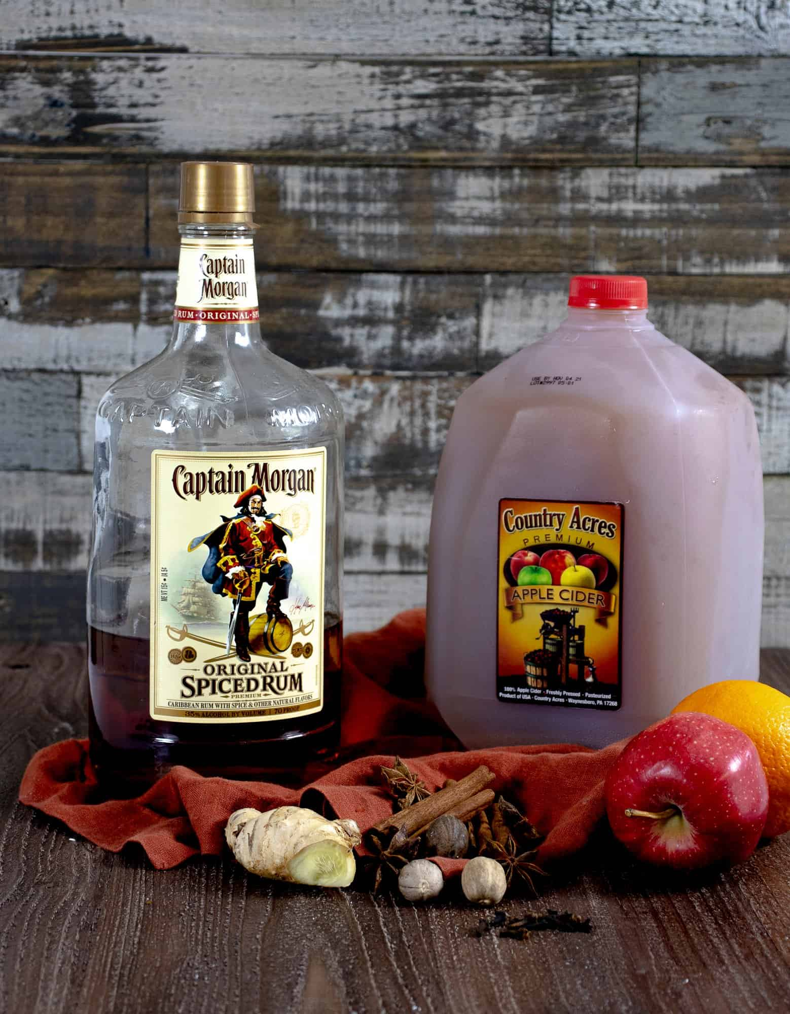 Spiced rum, apple cider, apples, oranges and spices on table to make your own homemade spiked apple cider.