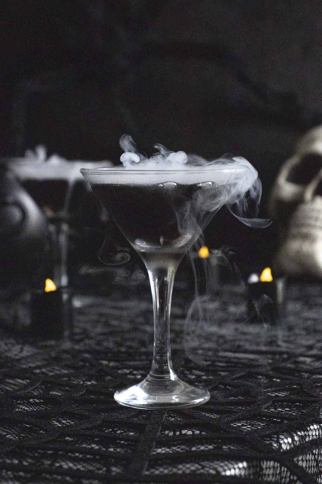 Black vodka witches martini on spooky table with smoke.