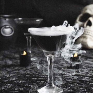 Black vodka martini with smoke on dark table.